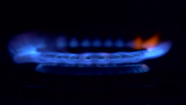 gas is switching on, apearing blue flame. gas stove on black background - пламя стоковые видео и кадры b-roll