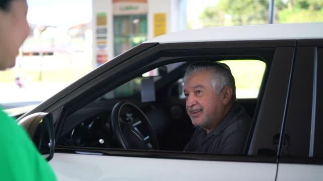 Gas station attendant talking to customer at car at service station