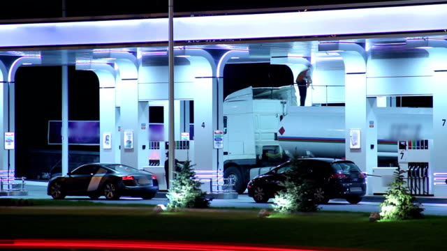 Gas station workers serve cars fueling vehicles, timelapse drive video
