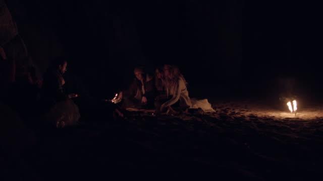 Gathering around log fire 4K - video