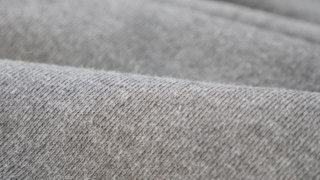 Gathers of grey training shirt or pants fine fabric pattern close-up 4K Gathers of grey training shirt or pants fine fabric pattern close-up 4K 2160p 30fps UltraHD tilting footage - Cotton and polyester sweater texture of cloth slow tilt 4K 3840X2160 UHD video sweatshirt stock videos & royalty-free footage