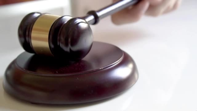 Gavel pounds on block in slow motion. video