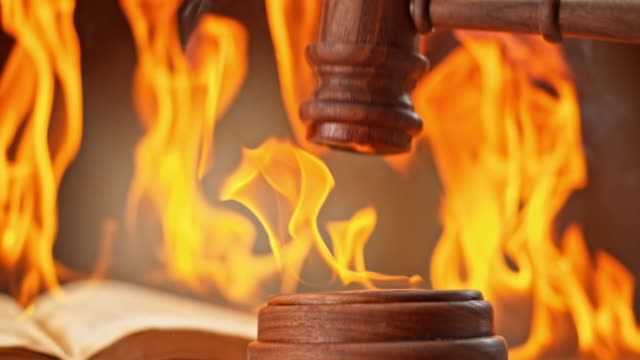 SLO MO LD Gavel striking a burning sound block on the desk with a book burning in the background video