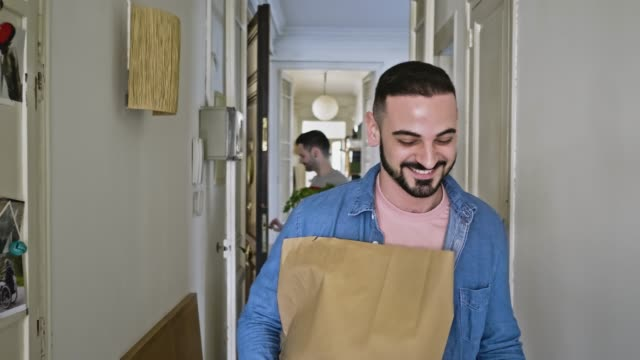 gay couple arriving back home with some shopping - portare video stock e b–roll