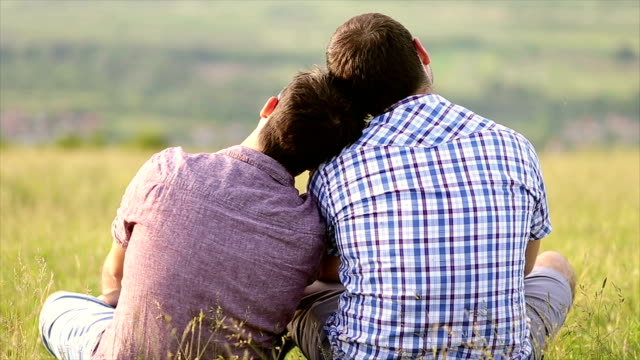 gay couple cuddling in the park - same sex couples stock videos and b-roll footage