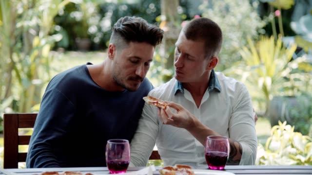 schwulenpaar essen pizza - gay man stock-videos und b-roll-filmmaterial