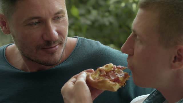 Gay couple eating pizza