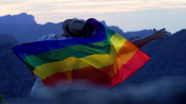 Gay couple gently lovingly hugging with rainbow flag video