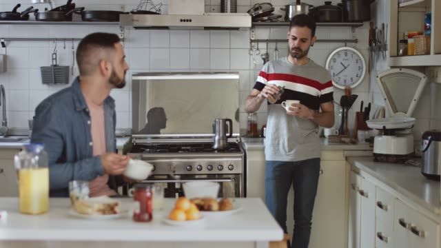 Gay couple having breakfast at home Gay couple having breakfast at home, one is sitting on the kitchen table while other is standing next to the coffee pot preparing the coffee while they are talking. human relationship stock videos & royalty-free footage