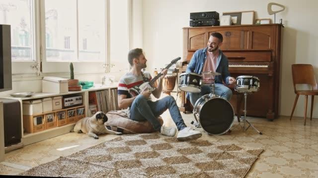 gay par ha roligt att spela musik hemma - trumset bildbanksvideor och videomaterial från bakom kulisserna