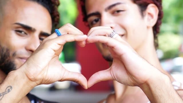 coppia gay che fa forma al cuore con le mani - love video stock e b–roll