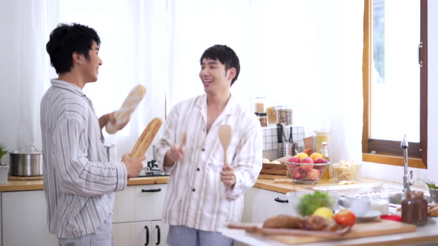 Gay couple man cooking in a kitchen Gay couple man cooking in a kitchen, Young Asian Gay couple man cutting vegetables in in the kitchen, Healthy foods and cooking concept nutritionist stock videos & royalty-free footage
