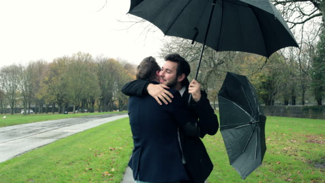 Gay couple meeting and hugging in the rain video