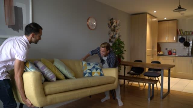 Couples homosexuels se déplaçant dans leur nouveau divan de portage de maison et s'asseyant sur lui étreignant et souriant - Vidéo