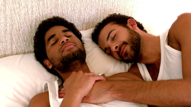 Gay couple relaxing in the bed Gay couple relaxing in the bed at home gay man stock videos & royalty-free footage