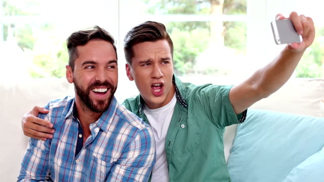 Gay couple relaxing on the couch taking selfie video
