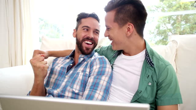 Gay couple relaxing on the couch using laptop Gay couple relaxing on the couch using laptop at home in the living room gay man stock videos & royalty-free footage