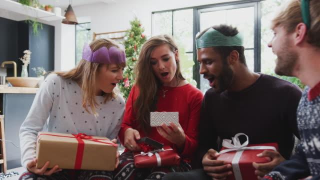 stockvideo's en b-roll-footage met gay vrienden thuis uitwisselen van geschenken op kerstdag samen - uitwisselen