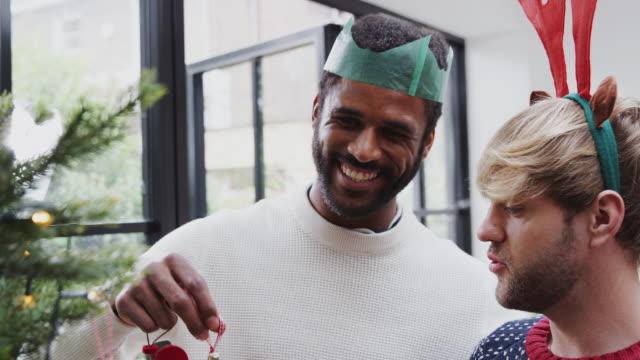homosexuell männliche paar zu hause hängen deko auf weihnachtsbaum zusammen - gay man stock-videos und b-roll-filmmaterial
