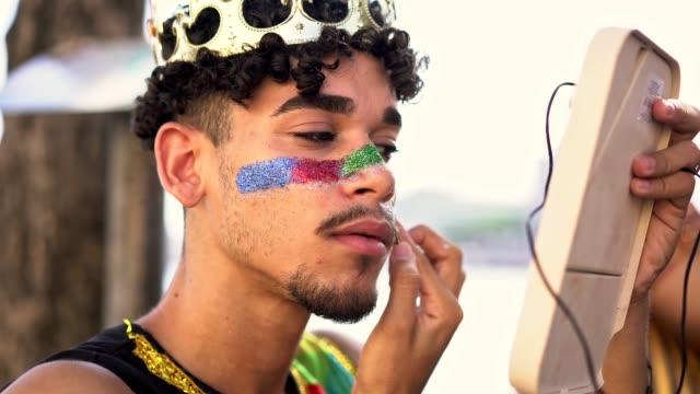 stockvideo's en b-roll-footage met gay man toepassing glitter op de huid - toneelschmink