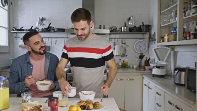 キッチンでパートナーにコーヒーを提供するゲイの男 - 同性カップル点の映像素材/bロール