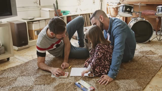 gay parents assisting daughter with drawing at home - tappeto video stock e b–roll