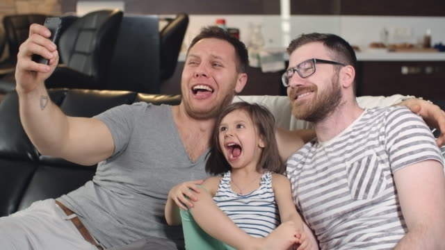 Gay parents taking funny selfies with cute daughter video