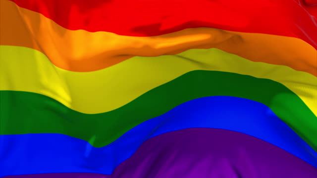 vídeos de stock e filmes b-roll de gay pride rainbow flag waving in wind slow motion animation . 4k realistic fabric texture flag smooth blowing on a windy day continuous seamless loop background. - bandeira