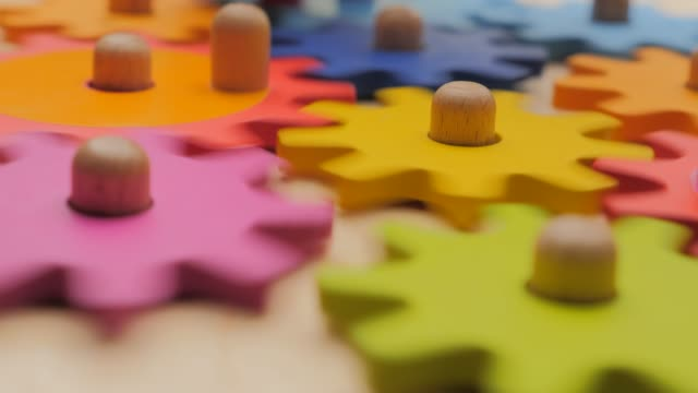Gears and cogs macro in colorful wooden toy. Team work concept. Connection background. Business concept. Working together. Simple mechanism. Mechanics basics