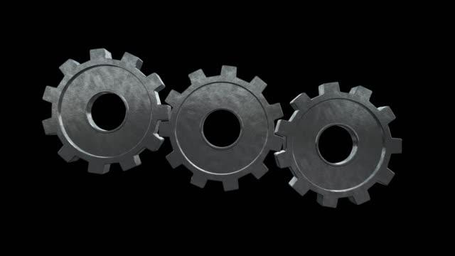vídeos de stock e filmes b-roll de gears spinning flies alone and become one gear. black background. alpha channel - três objetos