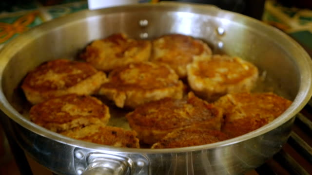 Gefilte fish frying in a stainless steel pan slow motion push in video