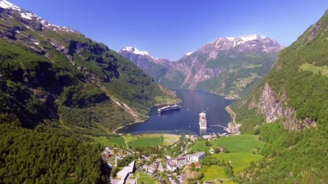 geiranger fjord area, norway. aerial view at summer time. fairytale landscape with its majestic, snow-covered mountain tops. fantastic view of one of most beautiful tourist destinations in the world - fiordo video stock e b–roll
