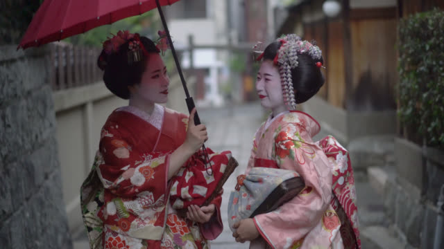 vídeos de stock e filmes b-roll de geishas enjoying a talk while walking outdoors and holding an umbrella - prefeitura de quioto