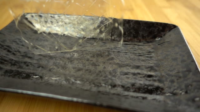 gelatin sheets falling into a black plate - super motion video