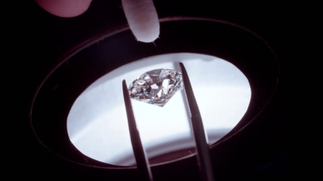 A gemologist inspecting a large clear diamond under a microscope