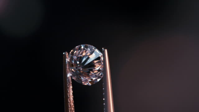 A gemologist inspecting a large clear diamond
