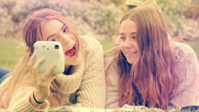 stockvideo's en b-roll-footage met gen z jonge vrouw vrienden met behulp van insta polaroid camera om selfie foto's te maken - polaroid