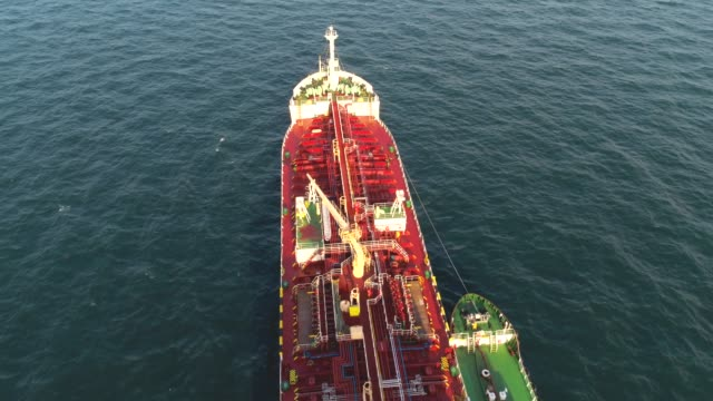General cargo ship at sea aerial footage. Shot. Aerial view of container ship passes through the channel goes into the open ocean