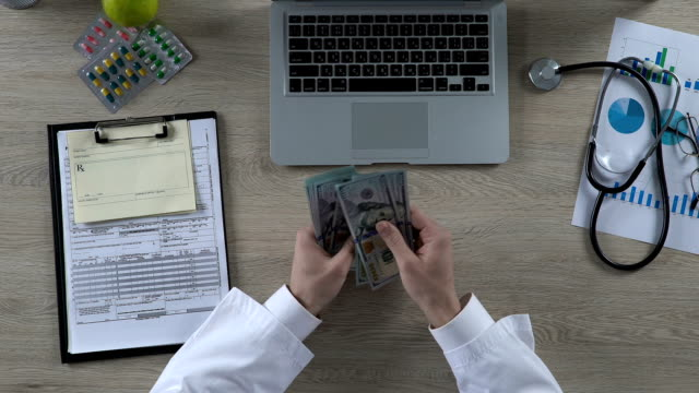 allmänläkare som räknar pengar tjänas på behandling av privat patient, pengar - lön bildbanksvideor och videomaterial från bakom kulisserna
