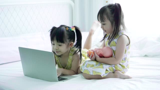 Generation Alpha-Two baby cute girls enjoy playing computer laptop and toy at the bedroom with positive emotion video