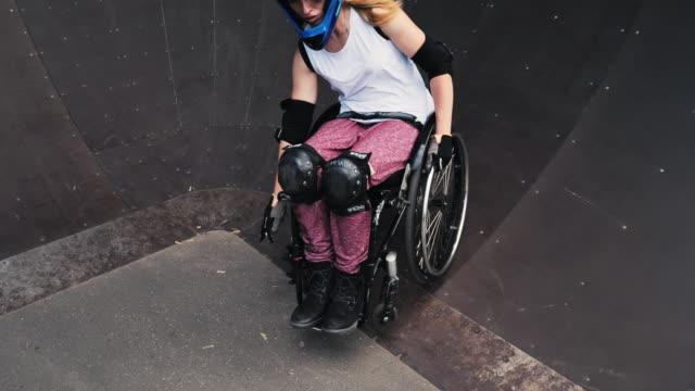 generation-z kvinna i rullstol i skate park gör stunts-slow motion video - skatepark bildbanksvideor och videomaterial från bakom kulisserna
