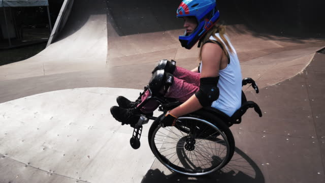 Generation-Z woman in wheelchair in skate park doing stunts - slow motion video Generation Z woman in wheelchair practicing stunts in skate park. Determination, courage and confidence shown in this extreme sport done by disabled woman. pushing wheelchair stock videos & royalty-free footage