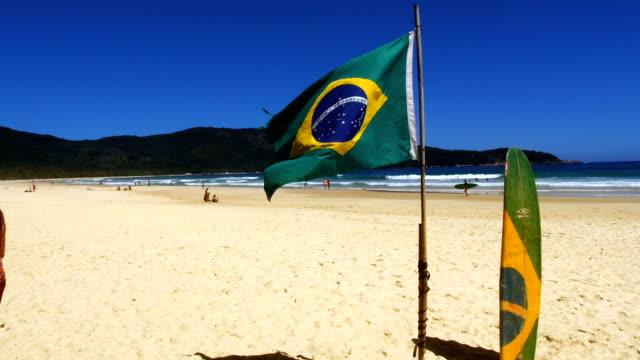 generic brasilianska beach med flaggan och surf board - brasilien flagga bildbanksvideor och videomaterial från bakom kulisserna