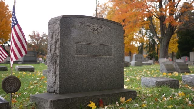 Generic grave marker in cemetery in autumn - veteran with flag ALT