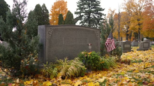 Generic grave marker in cemetery in autumn - veteran with flag