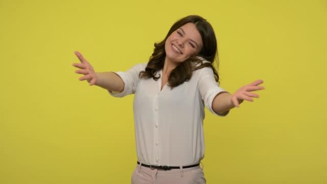 vidéos et rushes de femme généreuse de bon cœur avec le cheveu de brunette dans des chemisiers affichant le geste prennent tout, accueillant avec des bras grands ouverts - femme seule s'enlacer
