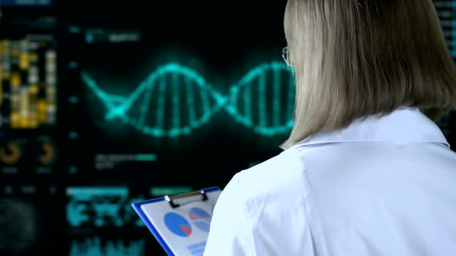 Geneticist watching DNA analysis process on screen, genetic modifications video