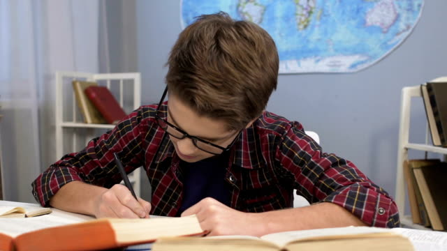 Genius boy in glasses doing homework task, writing answers in notebook, essay video