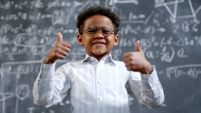 Genius Little Boy Posing Portrait shot of happy little African-American schoolboy in glasses standing before blackboard with complex calculus formula and showing thumbs up genius stock videos & royalty-free footage