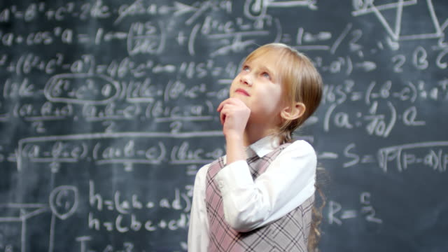 Genius Schoolgirl Thinking about Math Problem Portrait shot of cheerful schoolgirl standing against blackboard with complex calculus formulas thinking how to solve it genius stock videos & royalty-free footage